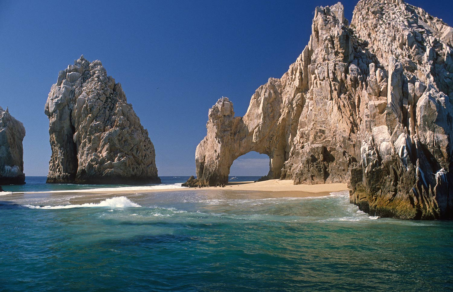 The famous stone arch at Land's End Cabo San Lucas with sand under the arch.